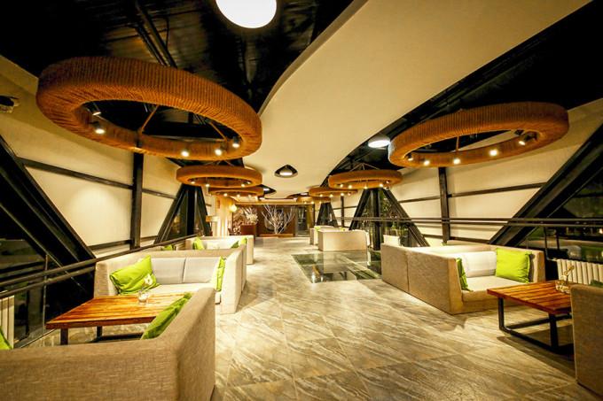 从整体来看,房间属于柔和中式室内设计,如原木房梁,老式木桌椅,陶瓷花